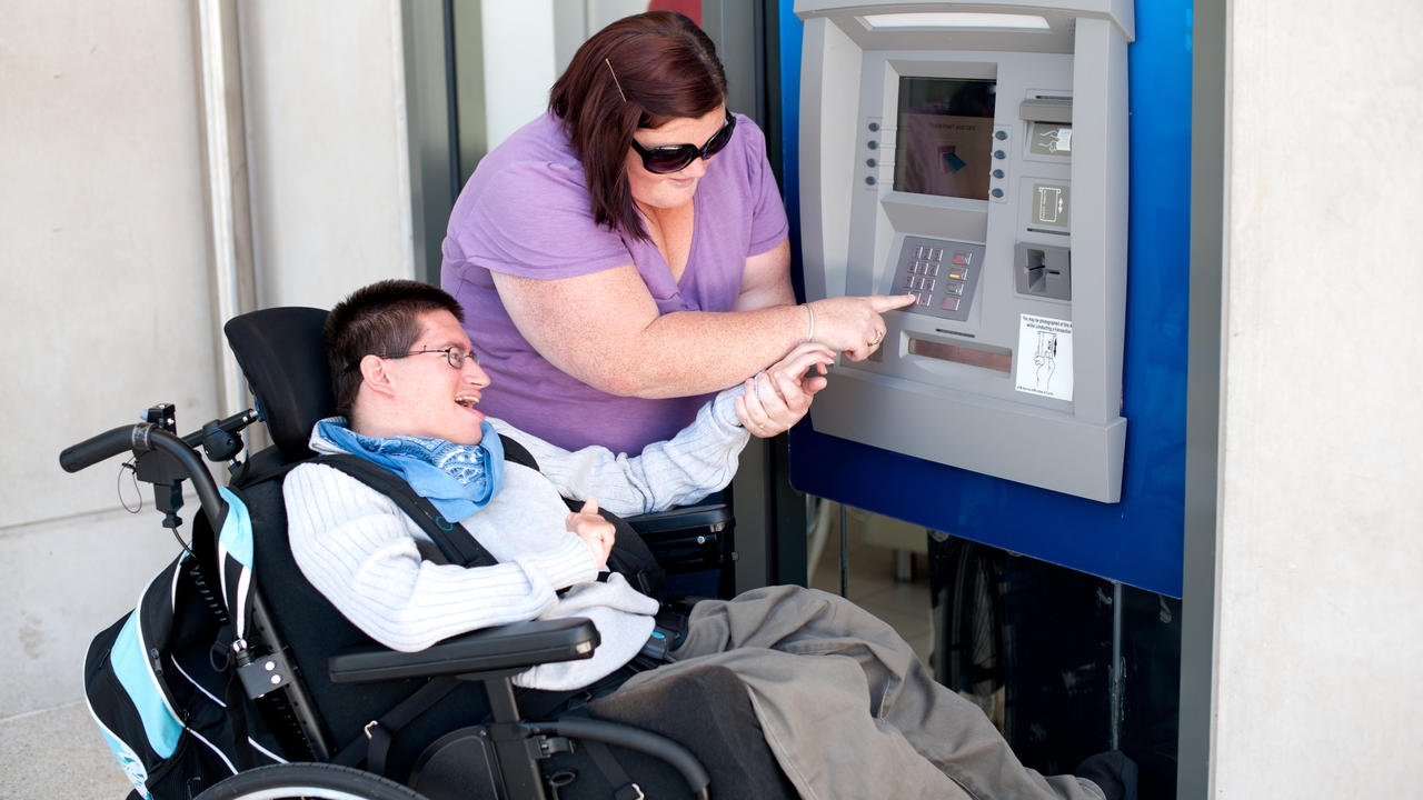 Woman helping a man with developmental disabilities use an ATM machine