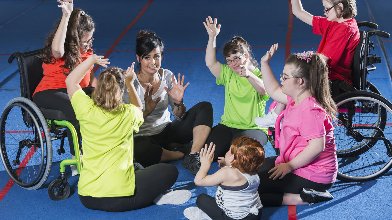 A group of people with developmental disabilities in a gym having fun during an activity