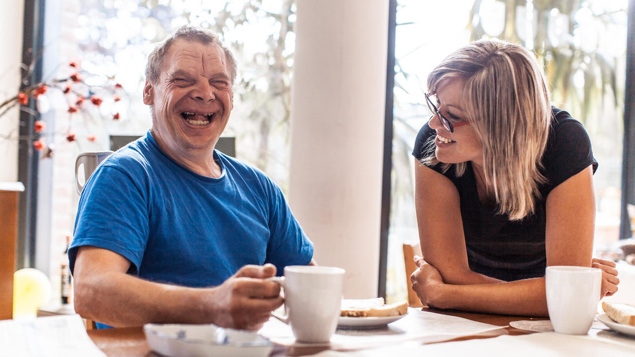 Smiling man with Down syndrome sitting in a kitchen with a caregiver