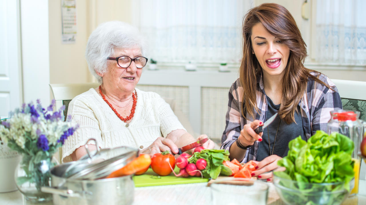 Young woman sitting next an elderly woman in her kitchen chopping vegetables