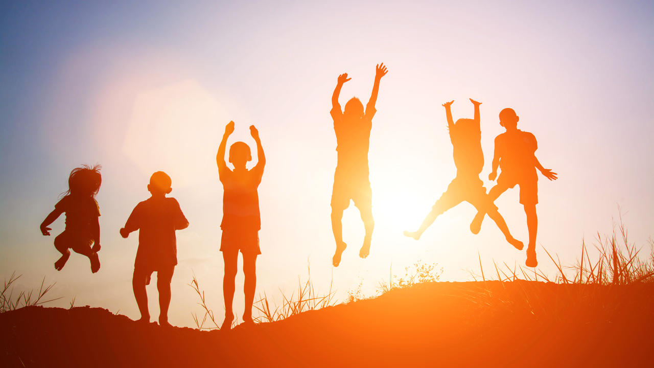 Silhouettes of children jumping in the sunset