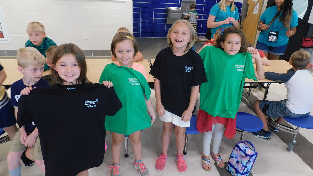 Smiling children holding up t-shirts that they won