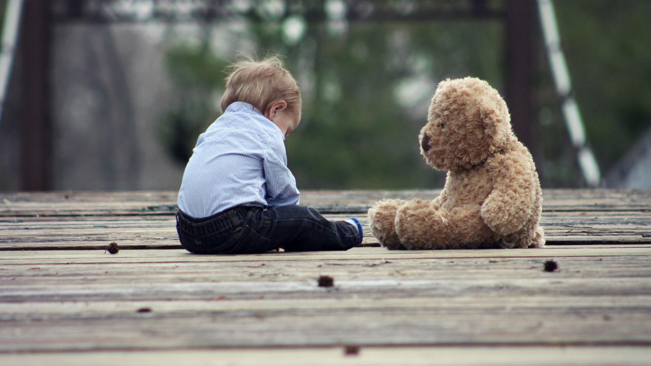 Young boy sitting next to a teddy bear