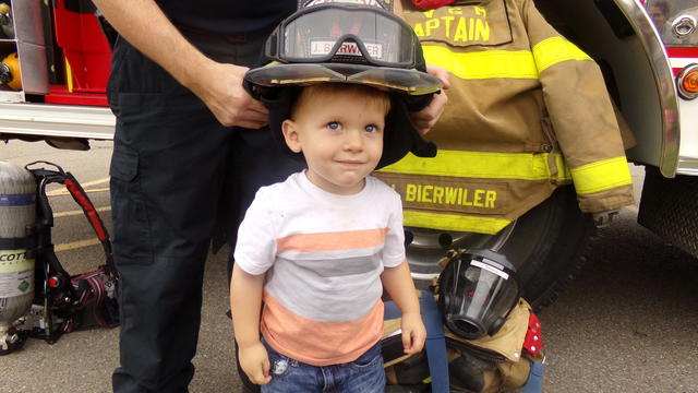 A little boy wearing a firemans helmet