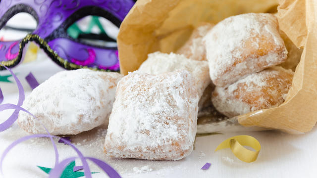 Beignets on a table with a Mardi Gras mask