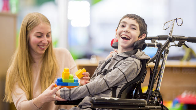 A young boy in a wheelchair having fun with his teacher