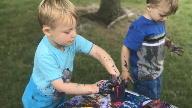 Boys playing with paint outdoors