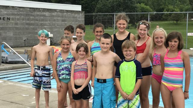 A group of children standing in front of a pool