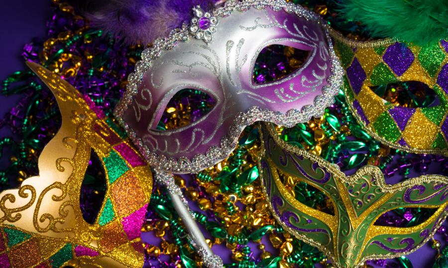 Mardi Gras masks laying on colorful beads